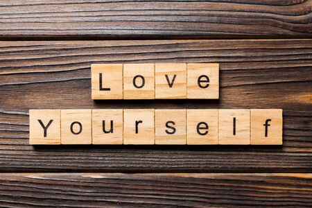 Love yourself word written on wood block. Love yourself text on wooden table for your desing, Top view concept.