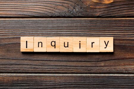 inquiry word written on wood block. inquiry text on table, concept.