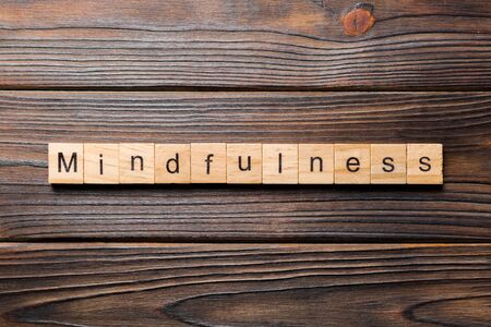 mindfulness word written on wood block. mindfulness text on table, concept.