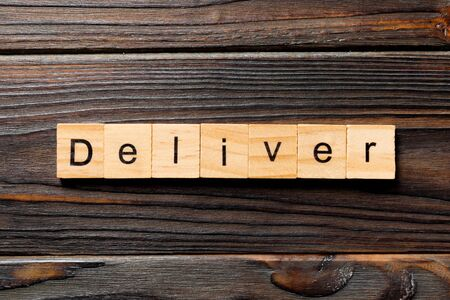 deliver word written on wood block. deliver text on table, concept.