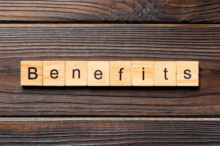 Benefits word written on wood block. Benefits text on wooden table for your desing, Top view concept.
