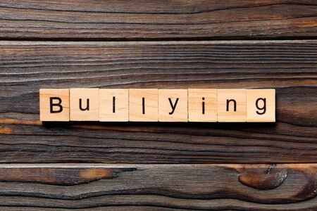 Bullying word written on wood block. Bullying text on wooden table for your desing, concept.
