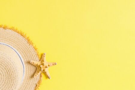 yellow retro straw hat with seastar top view with copy space. summer concept on yellow background.