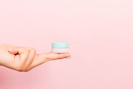 Close up of female hand holding a jar of cosmetics product at pink background with copy space.