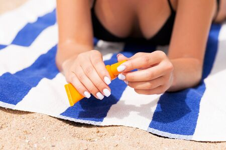 Beautiful lady is sunbathing on the towel on the sand at the beach and protects her hands with sunblock. Standard-Bild - 143192551