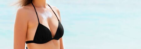 Beautiful young woman is enjoying sunshine at the beach with sun cream on her breast. Standard-Bild - 143192556
