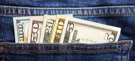 American dollar bills in jeans pocket background.