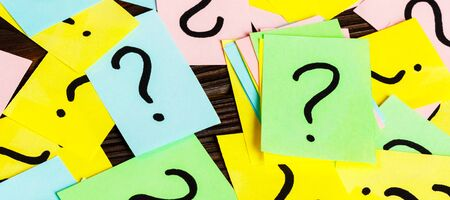 Pile of colorful paper notes with question marks on wooden background. Closeup.