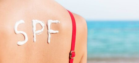 SPF word made of sunblock at woman's back at the beach. Sun protection factor concept.