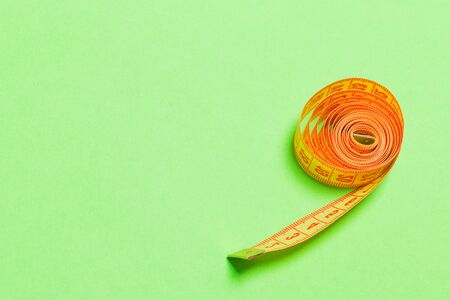 Tangled measuring tape with space for your idea. Sewing and tailor concept on green background.
