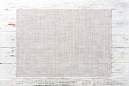 Top view of empty white tablecloth on wooden background with copy space.