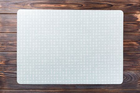 Top view of empty green table napkin for dinner on wooden background with copy space.