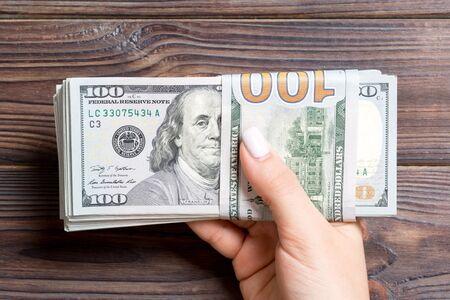 Top view of female hand holding a pack of one hundred dollar bills on wooden background. Wage and salary concept.