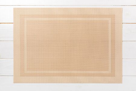 Top view of brown place mat for a dish. Wooden background with empty space for your design.