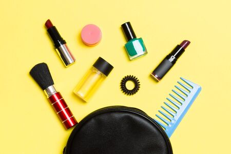 Top view od cosmetics bag with spilled out make up products on yellow background. Beauty concept with empty space for your design.