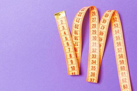 Top view of measuring tape on purple background. Tailor and slim waist concept with emty space for your idea. Stockfoto