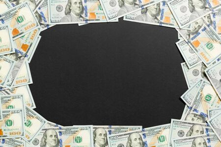 Frame of one hundred dollar bills with empty space for your design. Top view of business concept on black background with copy space. Reklamní fotografie