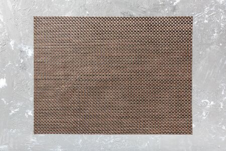 Top view of brown table napkin on cement background. Place mat with empty space for your design.
