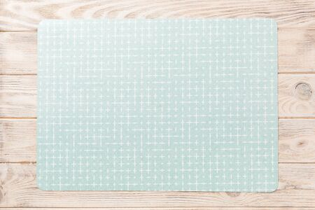 Top view of green place mat for a dish. Wooden background with empty space for your design.