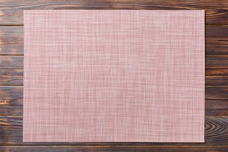 Top view of brown tablecloth for food on wooden background. Empty space for your design.
