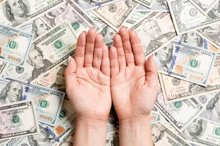 Top view of female hands on various dollar background. Wealth concept with empty space for your design. Begging money concept.