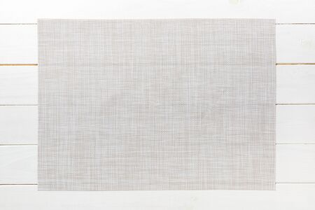 Top view of empty white table napkin for dinner on wooden background with copy space.