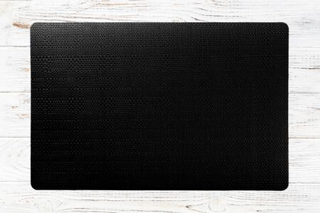 Top view of black place mat for a dish. Wooden background with empty space for your design.