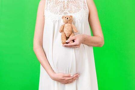 Cropped image of teddy bear in hand against pregnant woman's belly in white dress at green background. Waiting for a childbirth. Copy space.