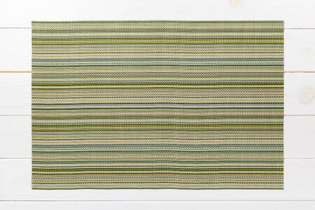 Top view of green table napkin on wooden background. Place mat with empty space for your design. Archivio Fotografico