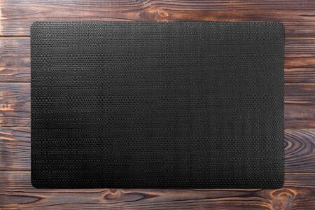 Top view of black table napkin on wooden background. Place mat with empty space for your design.