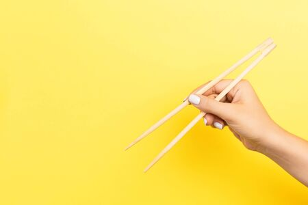 Girl's hand showing chopsticks on yellow background. Asian cuisine concept with empty space for your design.