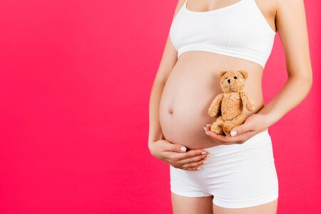 Close up of teddy bear in pregnant woman's hand at pink background. Future mother is wearing white underwear. Naked belly. Motherhood concept. Copy space. Standard-Bild