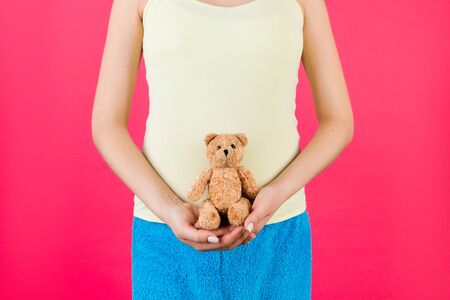 Cropped image of happy pregnant woman in colorful home clothing holding teddy bear against her belly at pink background. Child expecting. Copy space. Archivio Fotografico