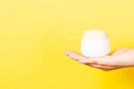 Close up of female hand holding cosmetics jar at yellow background with copy space.