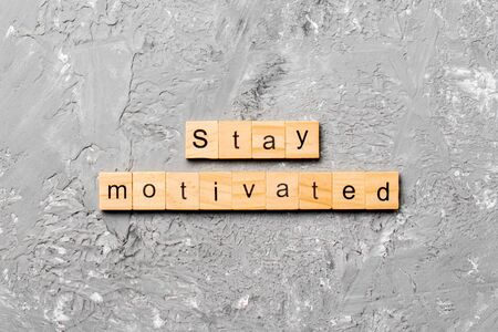 Stay motivated word written on wood block. Stay motivated text on cement table for your desing, concept.