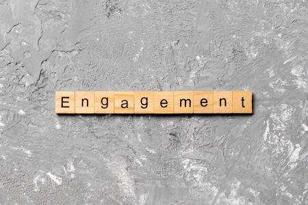 engagement word written on wood block. engagement text on table, concept. Imagens
