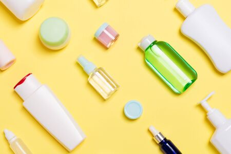 Top view of different cosmetic bottles and container for cosmetics on yellow background. Flat lay composition with copy space.