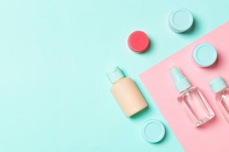 Top view of cosmetic containers, sprays, jars and bottles on pink background. Close-up view with empty space for your design. Archivio Fotografico