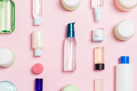 Group of plastic bodycare bottle Flat lay composition with cosmetic products on pink background empty space for you design. Set of White Cosmetic containers, top view with copy space. Archivio Fotografico