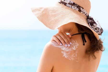 Beautiful woman in hat is putting sun cream on her shoulder at the beach.
