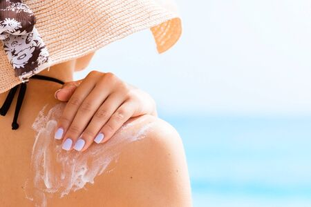 Sunscreen sunblock. Woman in a hat putting solar cream on shoulder outdoors under sunshine on beautiful summer day.