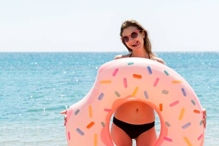Beautiful woman is playing with donut rubber ring and showing her tongue on the beach at the sea background. Standard-Bild