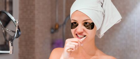 Portrait of young woman with black eye patches and wrapped in towel after shower is cleaning her teeth in front of the mirror. Tooth hygiene.