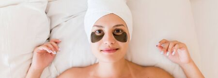 Young woman with black patches under her eyes is lying and relaxing in the bed after having a bath wrapped in towel. Beauty treatment and skincare concept. Фото со стока