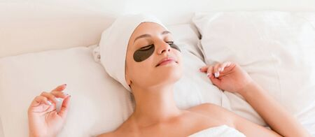 Young woman with closed eyes and black eye patches is lying and relaxing in the bed after having a bath wrapped in towel. Beauty treatment and skincare concept. 版權商用圖片