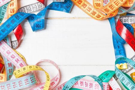 Heap of colorful measuring tapes in the form of frame on wooden background. Top view of slim waist concept with copy space.