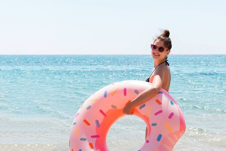 Beautiful woman is playing with donut rubber ring on the beach at the sea background.