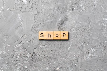 shop word written on wood block. shop text on cement table for your desing, concept.