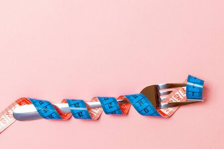 Diet concept with fork wrapped in measuring tape on pink background. Top view of weight loss with empty space.