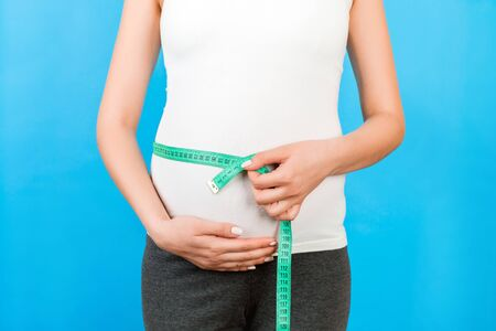 Cropped portrait of pregnant woman in home clothing is measuring her growing belly at blue background. Happy pregnancy. Copy space.